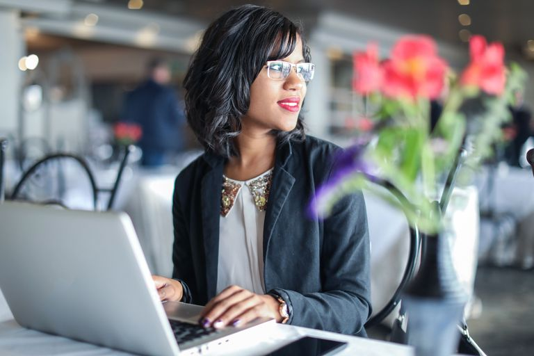 Woman wearing glasses looking out a nearby window while using her computer