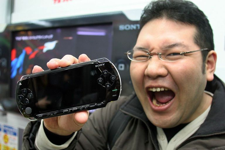 An excited guy holds a Sony PlayStation Portable (PSP)