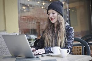 Woman at outdoor table with Macbook Pro covered by case