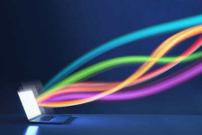 Beams of light representing data flow into a laptop