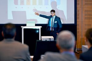 Man in suit presenting to a group of people