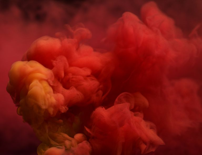 Red colored smoke that rises up and mixes in beautiful abstractions