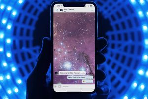 Close up of iPhone X with BBM on its screen in front a blue background