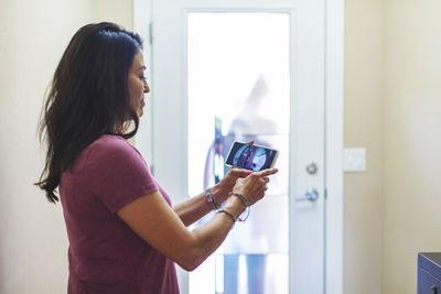 A woman viewing the feed from her smart doorbell on her phone.