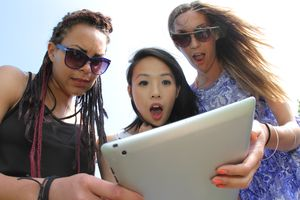 A group of friends holding an iPad tablet