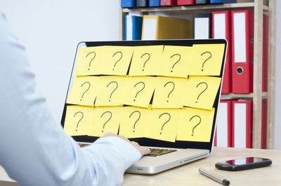 An image of a laptop covered in post-it notes of question marks.