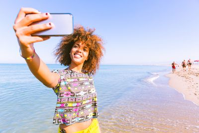 Tourist taking a selfie on the shore of the ocean