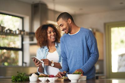 Screenshot of couple looking at phone with food in front of them on a table
