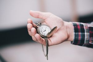 Man holding a pocket watch outside