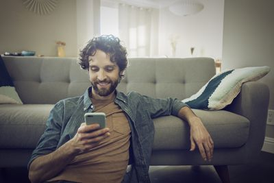 A man sitting on the floor leaning against a sofa while smiling at his smartphone