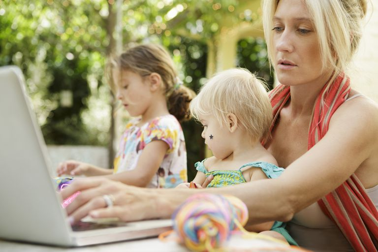 Mom using computer outside with two children next to her