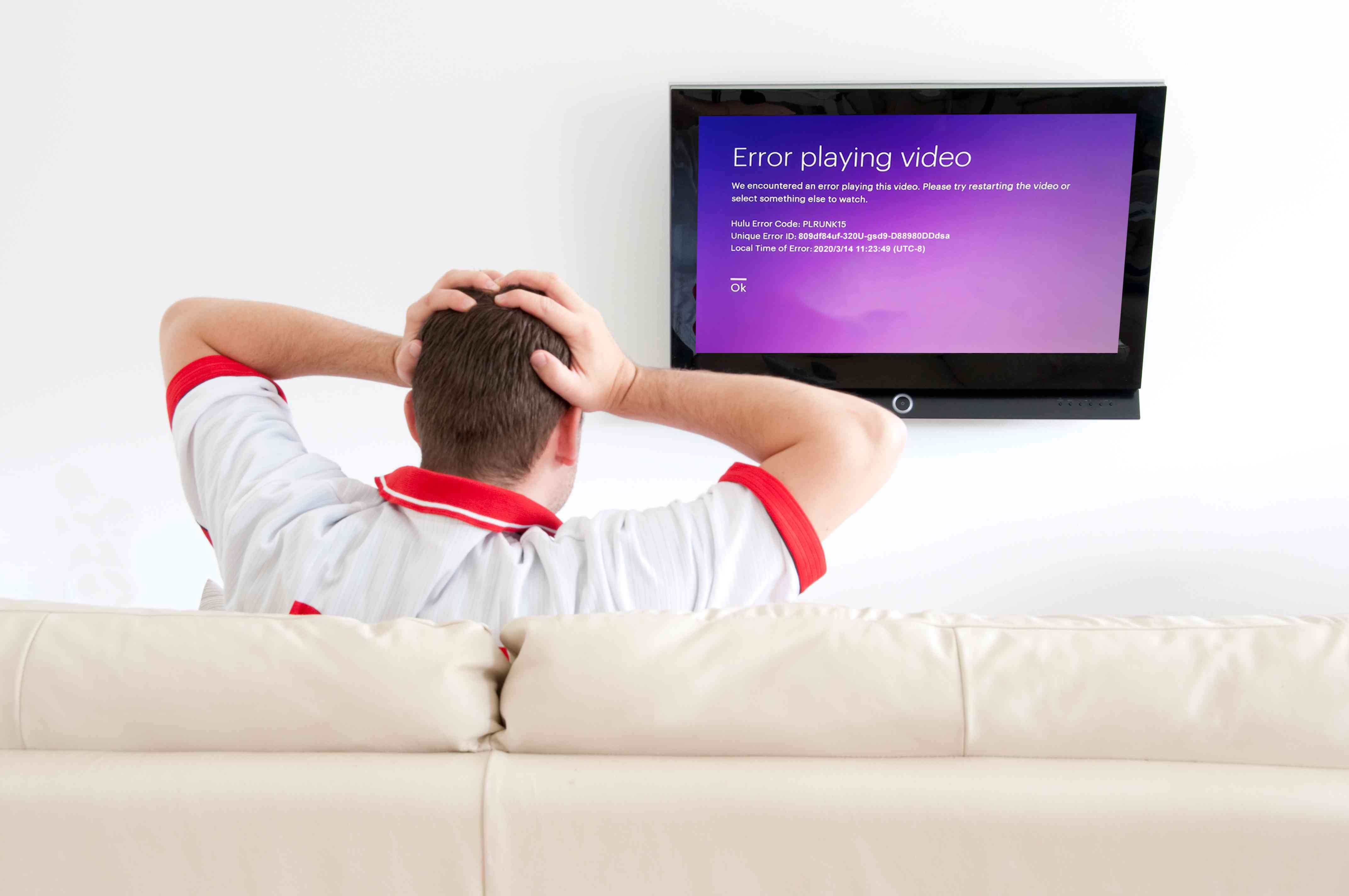 Hulu error code PLRUNK15 appears on a frustrated man's television.