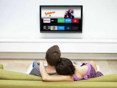Couple on couch downloads apps on their Fire TV Stick.