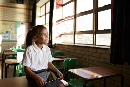 Girl in school holding a tablet as the light shines through her classroom's windows