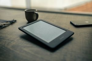A Kindle e-reader sitting on a table top with a cup of coffee and an iphone nearby.