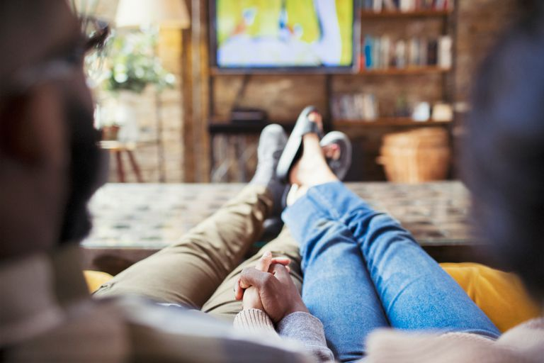 Shot over the shoulder of a couple sitting on couch holding hands watching television