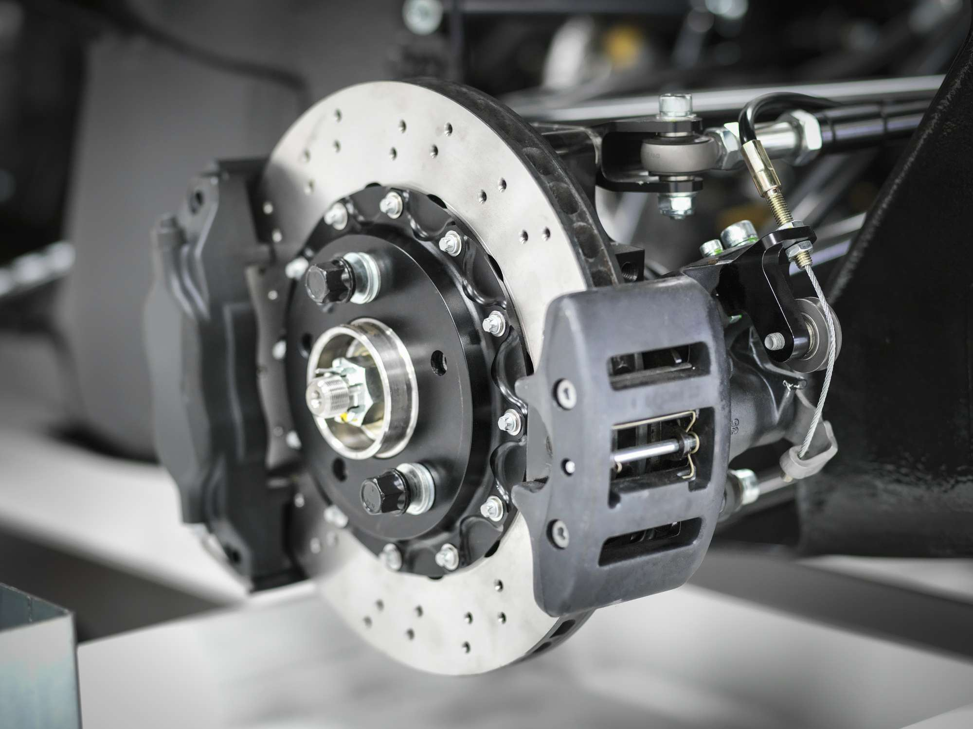 Detailed closeup of a brake rotor, calipers, and other equipment.