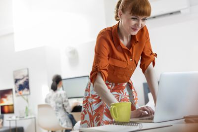 Businesswoman standing typing at laptop in office