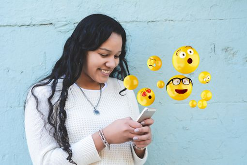 An image of a woman typing emojis on a smartphone.