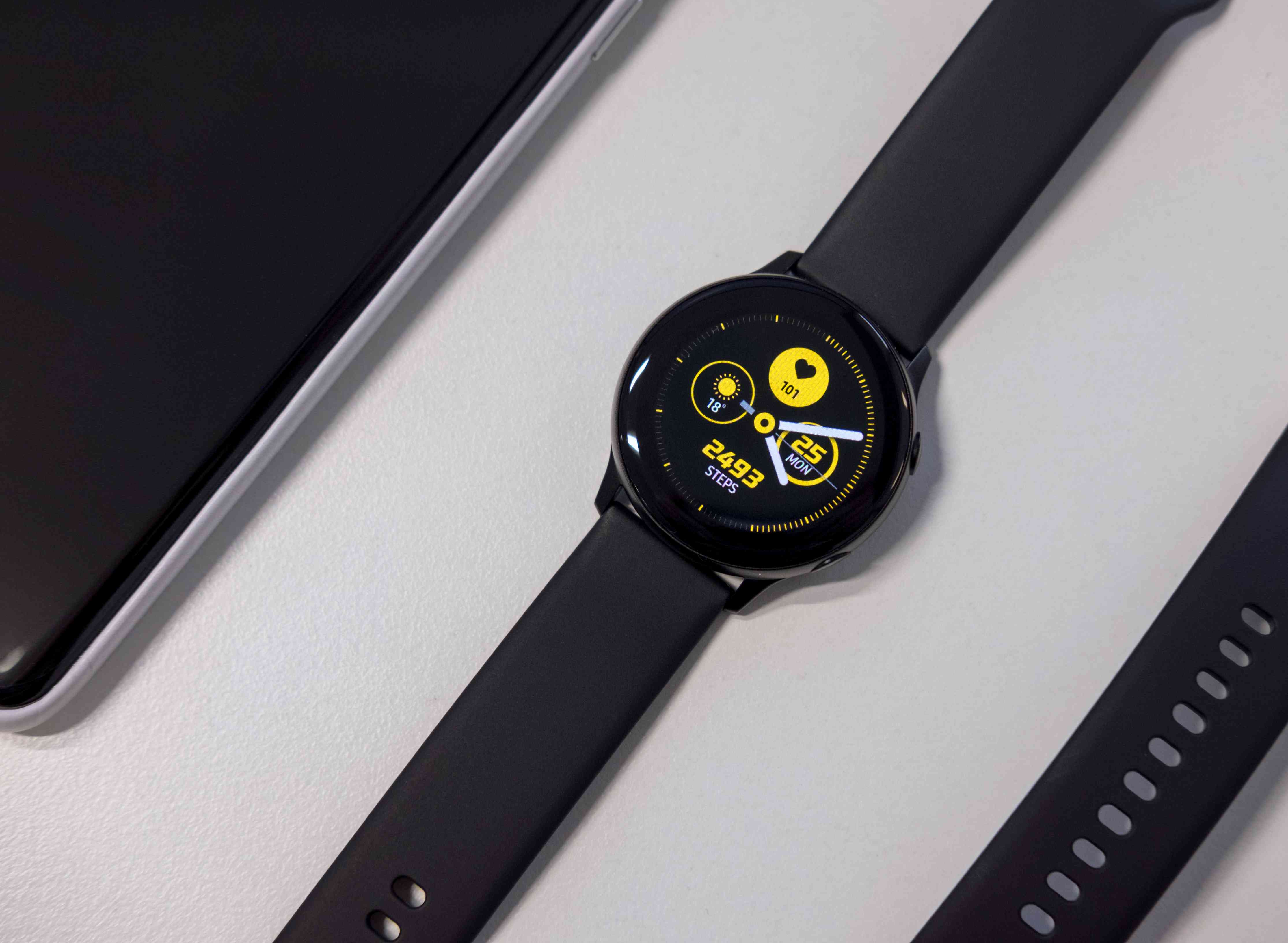 A black smartwatch with yellow complications showing on the face.