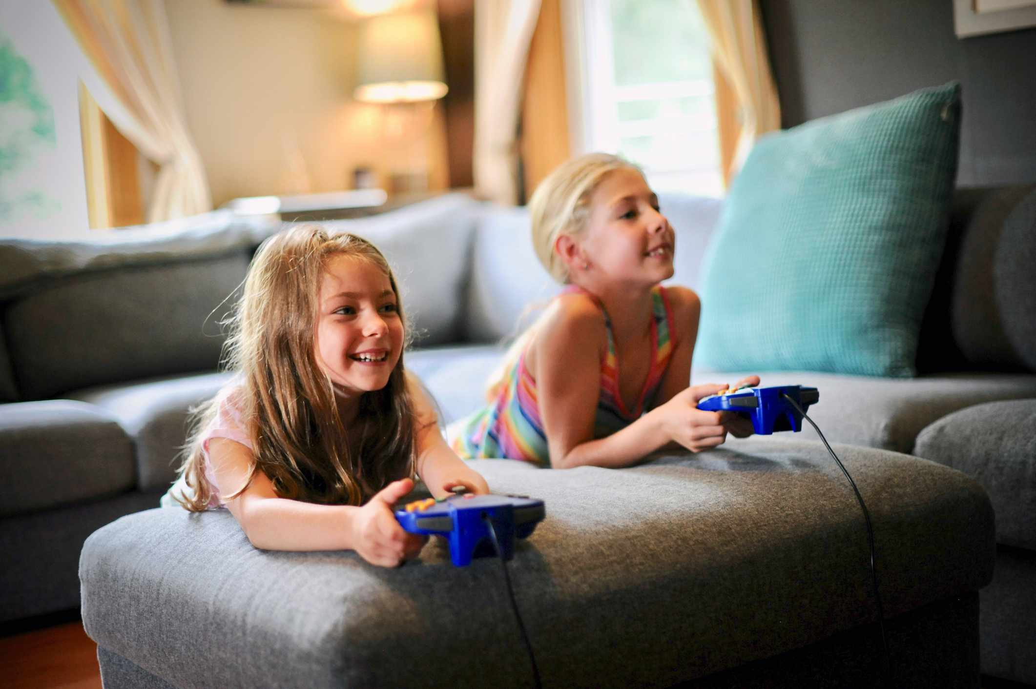 Two young children playing video games at home in the living room.