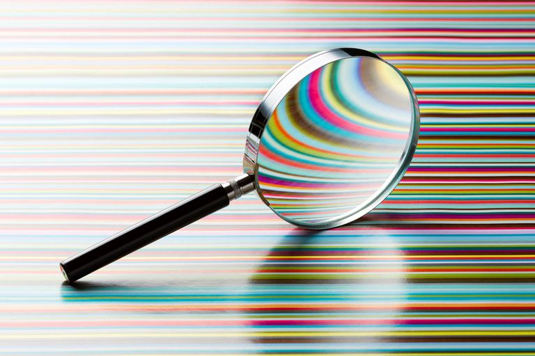 A magnifying glass on a colorful lined background