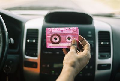 Hand in car holding pink audio cassette