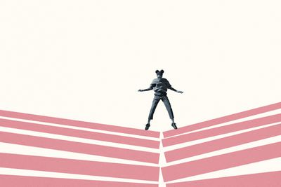 Young woman looking down while jumping on broken pink block stacks against white background.