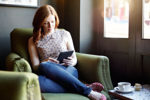 Woman sitting on green chair with E-reader