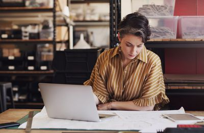 Woman working at a laptop and reading papers