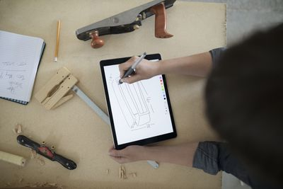 Carpenter sketching with a digital tablet stylus at a workbench in a workshop