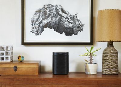 A Sonos One smart speaker sitting on a table with a lamp, plant, and other trinkets.