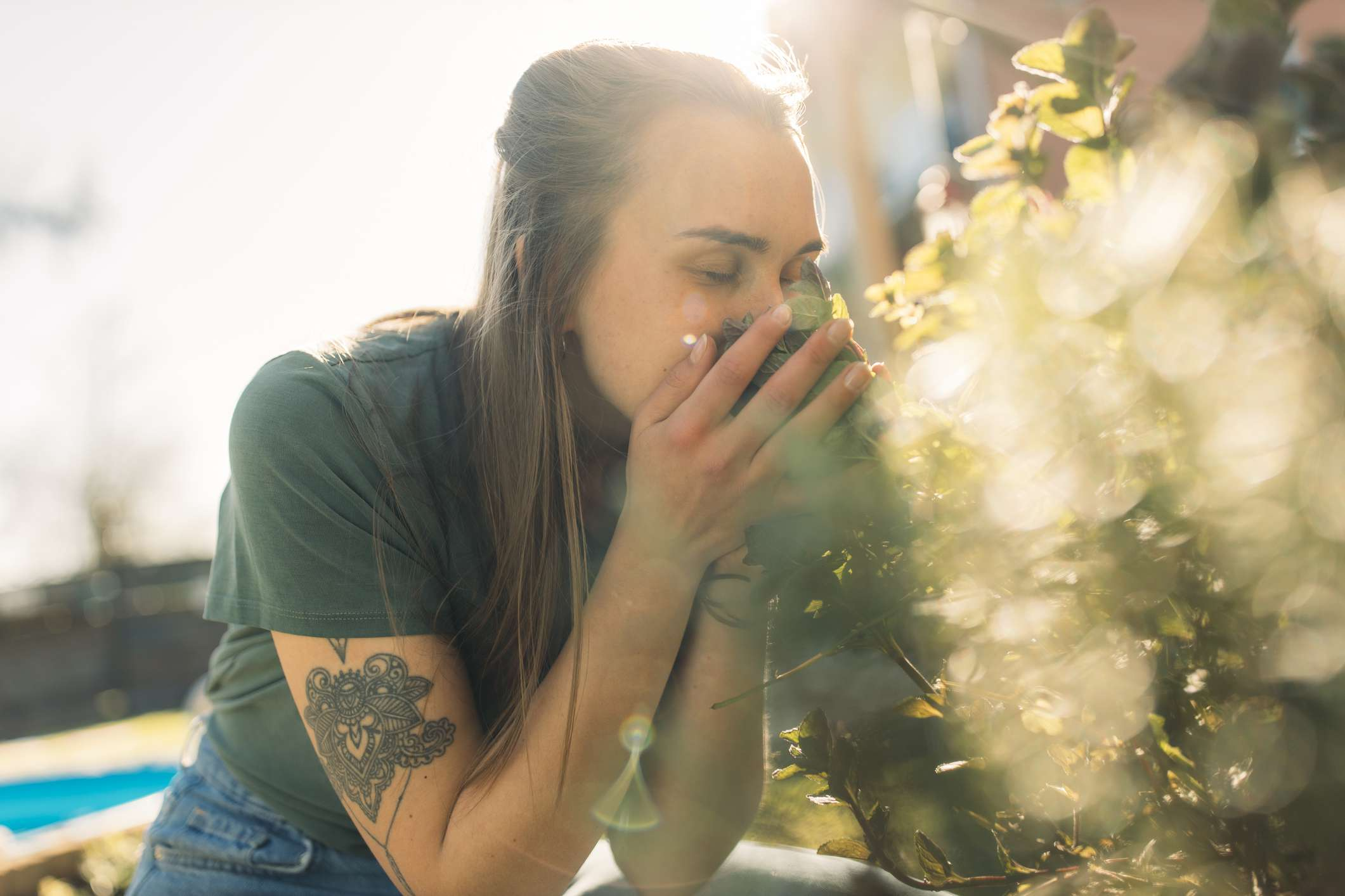 woman smelling herbs in a garden