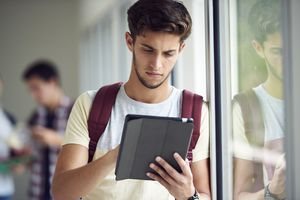 Student standing by window using tablet device