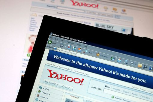The Yahoo! logo on a laptop with the page overlaying the background.