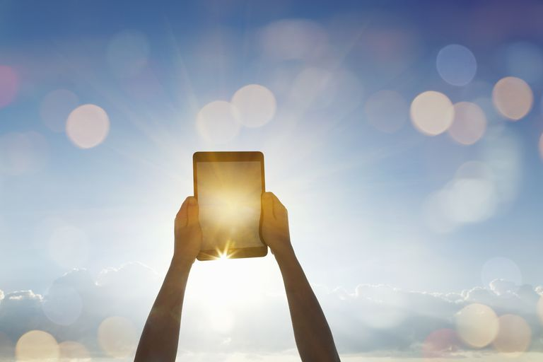 Woman's arms pointing a tablet toward the sun
