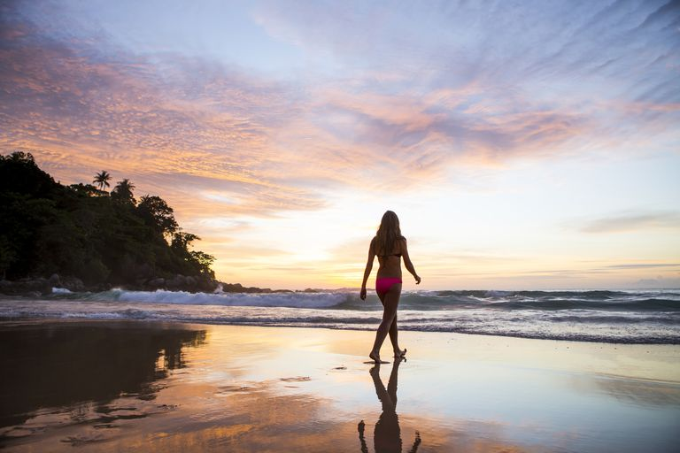 Woman walking on the beach with the sunsetting behind her