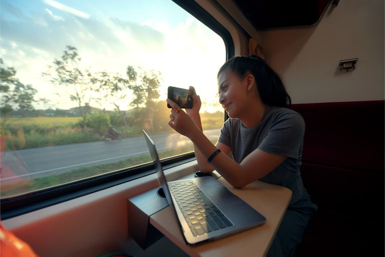 Women taking a photo of the landscape out of a moving train