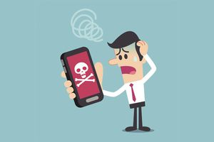 A frustrated person looking at a phone with a skull on its screen