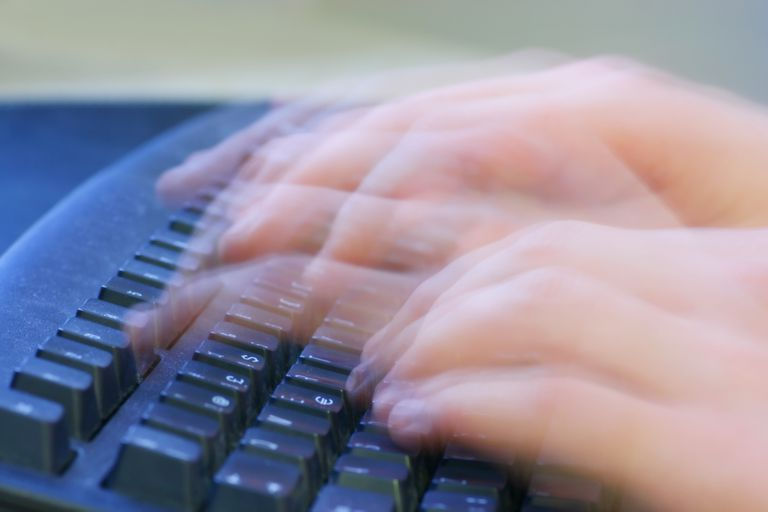 Image of hands moving quickly over a keyboard.