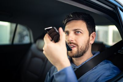 Someone in their car talking at their smartphone as if talking to a virtual assistant.