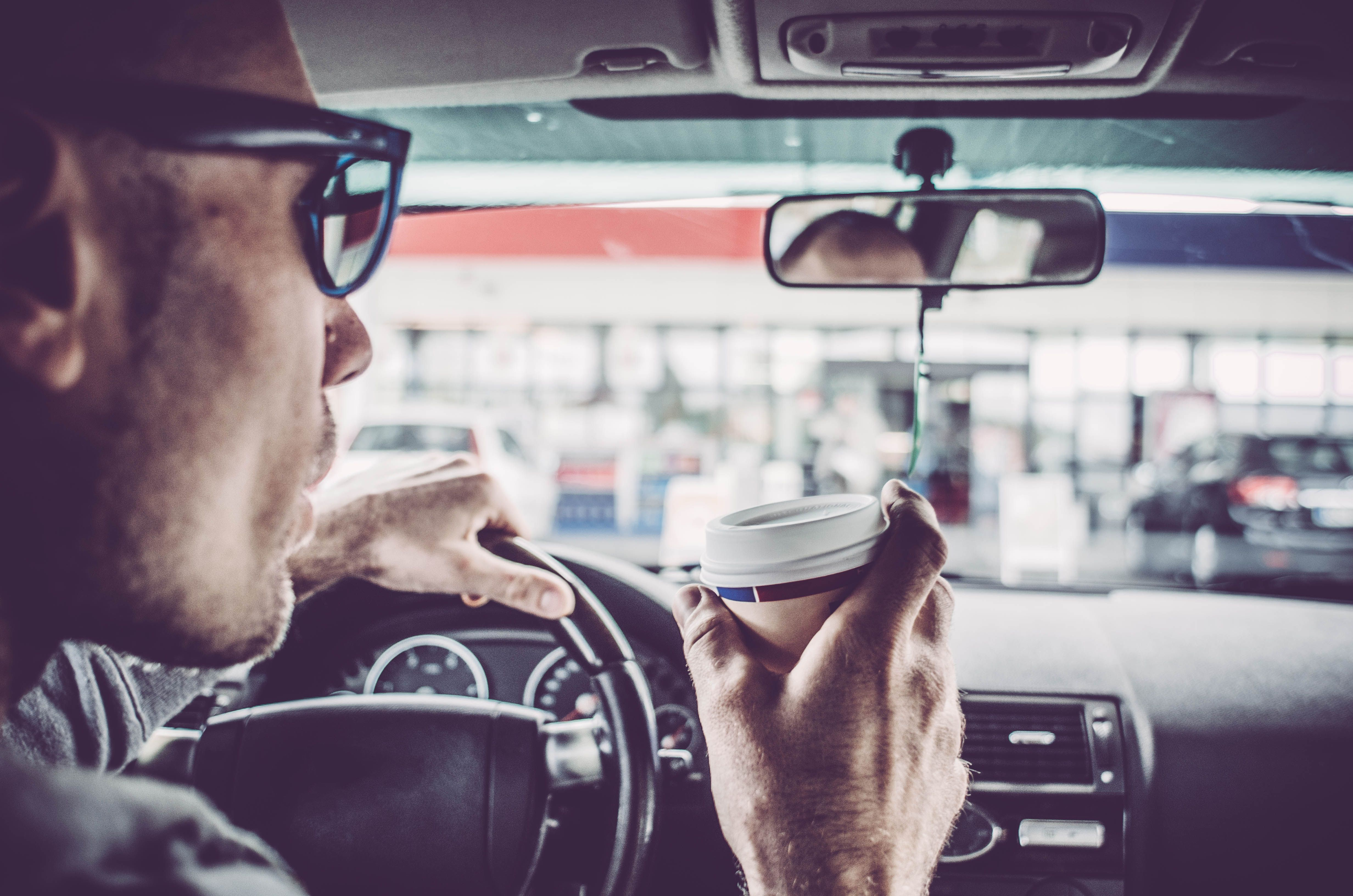 Man driving his car and drinking coffee