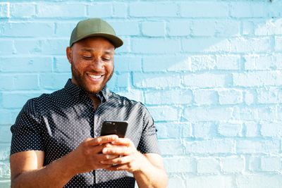 A man standing while holding his phone in his hands. He's smiling at it.