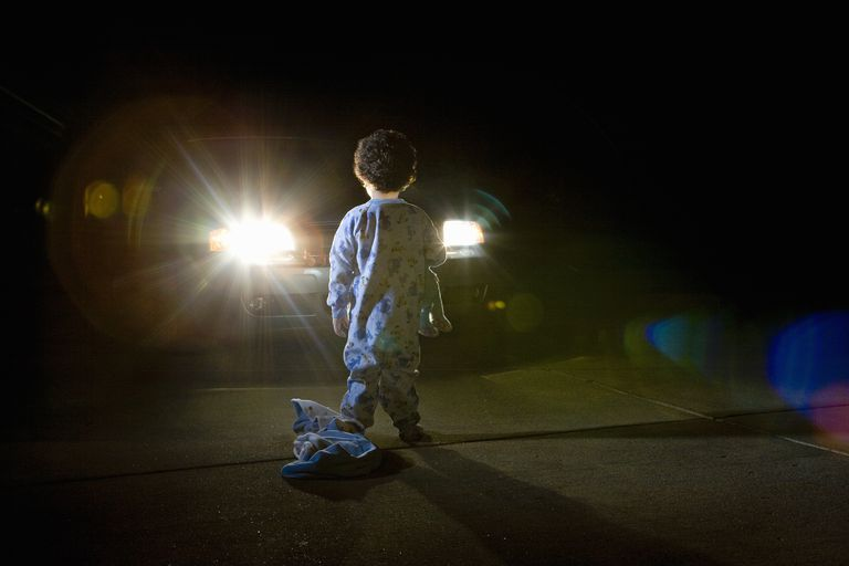 Child standing in front of oncoming car at night