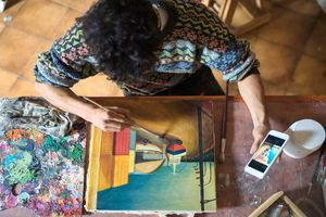 A painter using a color app on their smartphone.