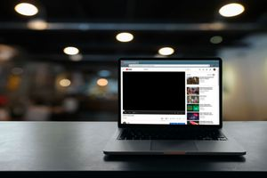 A laptop displaying a black screen on YouTube.