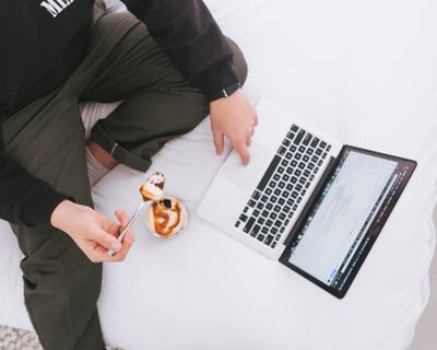 Person on laptop while eating, view from above.