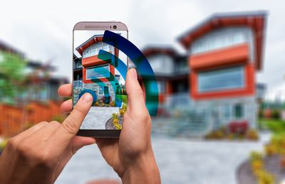 This screenshot shows a person using a smartphone to snap a photo of a house.