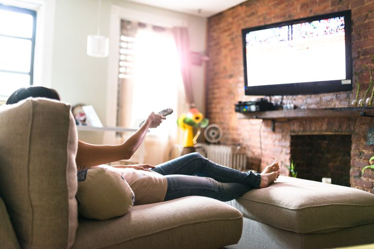 Woman watching TV on couch