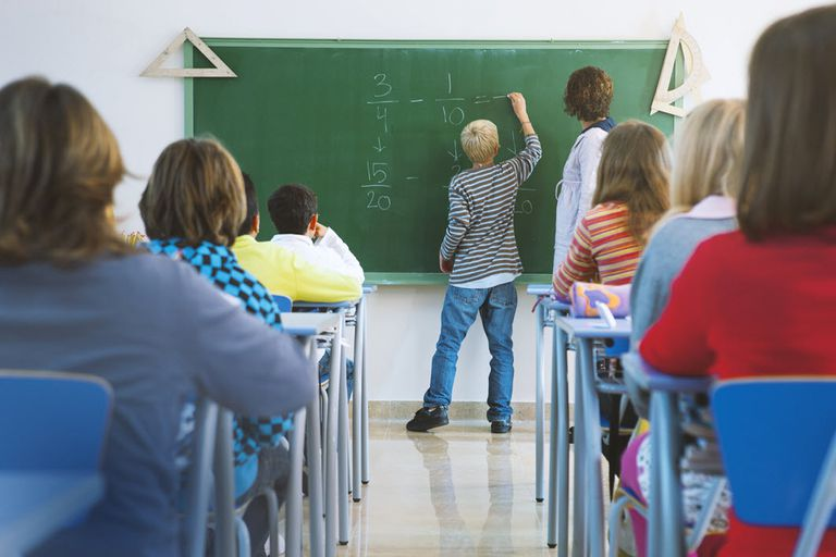 Student doing SUMs on blackboard surrounded by teach and other students.